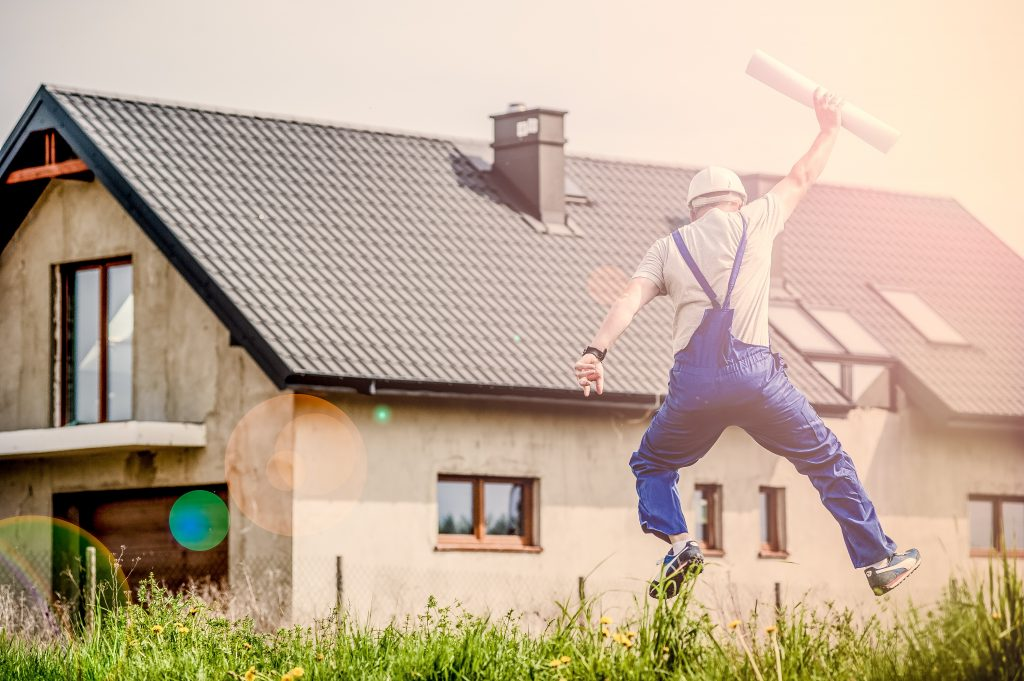 Man jumping with building plans and house in background